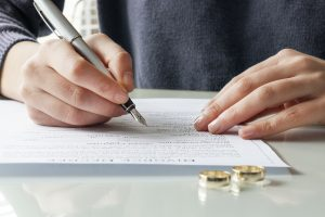 Man and woman signing divorce papers with wedding rings on desk
